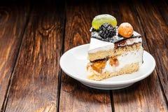 rebanada de la torta de la baya del chocolate en la placa sobre fondo de madera marrón Imágenes de archivo libres de regalías