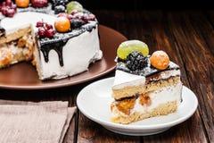 rebanada de la torta de la baya del chocolate en la placa sobre fondo de madera marrón Fotografía de archivo