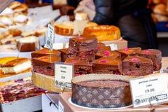 Rebanada de la torta de la frambuesa del chocolate en la exhibición en el mercado de la ciudad imagen de archivo