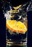 Rebanada de naranja que cae abajo en vidrio con agua Imagen de archivo libre de regalías