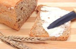 Rebanada de pan con mantequilla y oídos del trigo Fotos de archivo libres de regalías