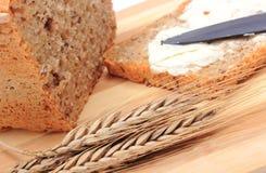 Rebanada de pan con mantequilla y oídos del trigo Fotografía de archivo libre de regalías