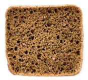 Rebanada de pan de centeno integral fresco en un blanco Imagen de archivo libre de regalías