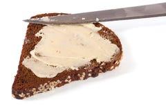 Rebanada de pan negro con las semillas y la mantequilla de sésamo aisladas en el fondo blanco Foto de archivo