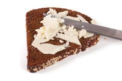 Rebanada de pan negro con las semillas y la mantequilla de sésamo aisladas en el fondo blanco Imagen de archivo libre de regalías