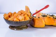 Rebanada de papaya aislada en la tabla blanca imagen de archivo