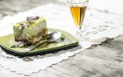 Rebanada de pastel de queso de la cal adornada con las flores de la menta y el vidrio del coñac, fondo borroso Fotografía de archivo