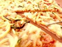 Rebanada de pizza con las patatas y el calabacín imagen de archivo