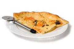 Rebanada de pizza en la placa blanca con el cortador de la pizza Imagen de archivo