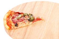 Rebanada de pizza en la tarjeta de corte de madera Fotos de archivo libres de regalías