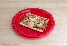 Rebanada de pizza en una placa roja encima de la tabla Fotografía de archivo libre de regalías