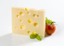 Rebanada de queso duro y de un tomate Imagen de archivo