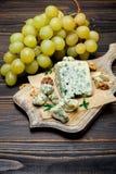 Rebanada de queso francés del Roquefort en el tablero de madera Foto de archivo libre de regalías