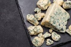 Rebanada de queso francés del Roquefort en el tablero de piedra Imagen de archivo libre de regalías
