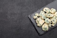 Rebanada de queso francés del Roquefort en el tablero de piedra Imagenes de archivo