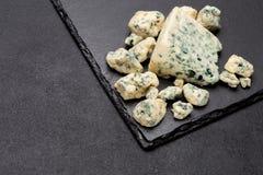Rebanada de queso francés del Roquefort en el tablero de piedra Fotos de archivo