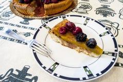 Rebanada de torta con la fruta en una placa blanca con la frambuesa imagen de archivo