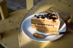 Rebanada de torta de café en plato en la tabla de madera Imagen de archivo