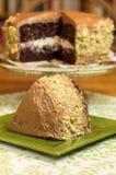 Rebanada de torta de chocolate con la torta en fondo fotografía de archivo libre de regalías