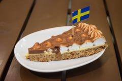 Rebanada de torta de la almendra con la bandera sueca Foto de archivo libre de regalías