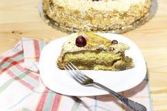 Rebanada de torta hecha en casa deliciosa con el café con leche adornado por la uva roja y las peras en la placa blanca en la tab Fotos de archivo
