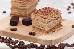Rebanada de torta de miel acodada con los granos de café Fotografía de archivo