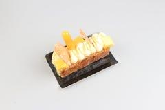 Rebanada de torta poner crema con el chocolate en un tablero blanco Imagen de archivo