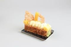 Rebanada de torta poner crema con el chocolate en un tablero blanco Fotografía de archivo