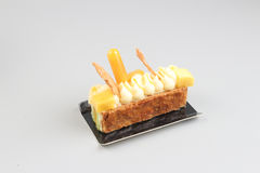 Rebanada de torta poner crema con el chocolate en un tablero blanco Foto de archivo libre de regalías