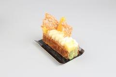 Rebanada de torta poner crema con el chocolate en un tablero blanco Foto de archivo