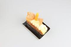 Rebanada de torta poner crema con el chocolate en un tablero blanco Fotografía de archivo libre de regalías