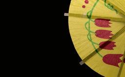 Rebanada de una decoración de papel amarilla del paraguas del cóctel en fondo negro Imagenes de archivo