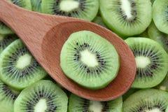 Rebanada del kiwi en una cuchara de madera Fotos de archivo