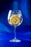rebanada del limón lanzada en un vidrio de agua Foto de archivo