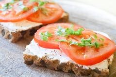 Rebanada del pan del cereal con el tomate y el ricotta Fotos de archivo