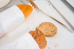 Rebanada del pan fresco y cuchillo de corte en la tabla en comida fría Foto de archivo