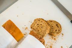 Rebanada del pan fresco y cuchillo de corte en la tabla en comida fría Imágenes de archivo libres de regalías