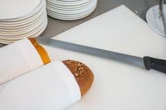 Rebanada del pan fresco y cuchillo de corte en la tabla en comida fría Fotos de archivo