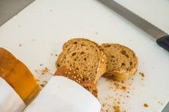 Rebanada del pan fresco y cuchillo de corte en la tabla en comida fría Imagenes de archivo