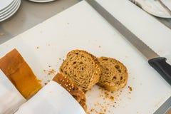 Rebanada del pan fresco y cuchillo de corte en la tabla en comida fría Fotos de archivo libres de regalías