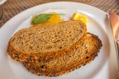 Rebanada del pan fresco y cuchillo de corte en la tabla en comida fría Fotografía de archivo libre de regalías
