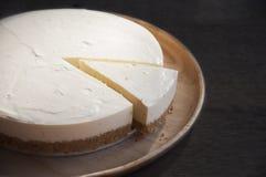 Rebanada del pastel de queso en la tabla Fotos de archivo