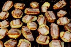 Rebanada grande de patatas del Pueblo-estilo en parrilla caliente del carbón de leña del Bbq Llamas del fuego en el fondo Imagen de archivo libre de regalías