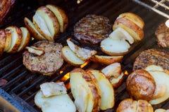Rebanada grande de patatas del Pueblo-estilo en parrilla caliente del carbón de leña del Bbq Llamas del fuego en el fondo Foto de archivo libre de regalías