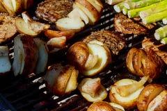 Rebanada grande de patatas del Pueblo-estilo en parrilla caliente del carbón de leña del Bbq Llamas del fuego en el fondo Imagen de archivo