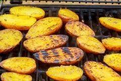 Rebanada grande de patatas del Pueblo-estilo en parrilla caliente del carbón de leña del Bbq Llamas del fuego en el fondo Foto de archivo