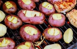 Rebanada grande de patatas del Pueblo-estilo en parrilla caliente del carbón de leña del Bbq Llamas del fuego en el fondo Imágenes de archivo libres de regalías
