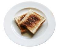 Rebanada quemada del pan de la tostada en el plato, backround blanco aislado Imagen de archivo libre de regalías