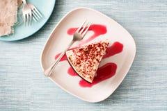 Rebanada roja de la torta del terciopelo en fondo azul Fotografía de archivo