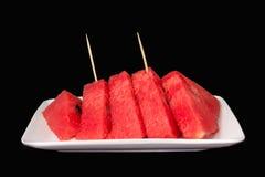 Rebanada roja del melón en el plato blanco Imagen de archivo